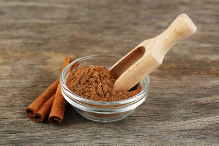 'cinnamon bark': Cinnamon bark and cinnamon powder on wooden table