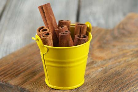 'cinnamon bark': Cinnamon bark in pail on wooden table
