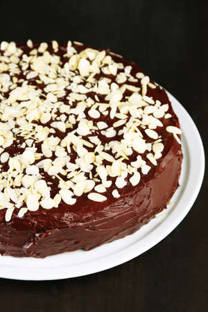 Tasty chocolate cake with almond, on wooden table photo