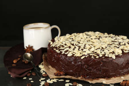 Tasty chocolate cake with almond, on wooden table, on dark background photo