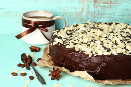 Tasty chocolate cake with almond, on old wooden table photo