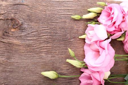 Beautiful eustoma flowers on wooden background photo