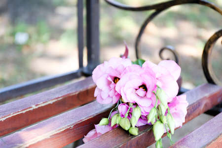 Beautiful bouquet of eustoma flowers on wooden bench in park photo