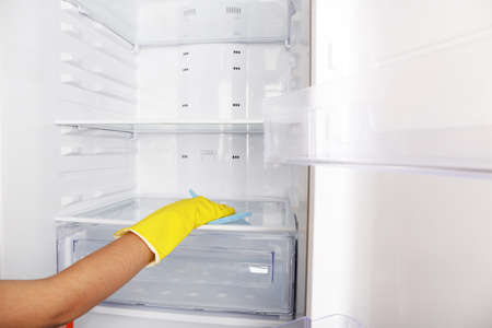 refrigerator: Womans hand washing refrigerator with duster Stock Photo
