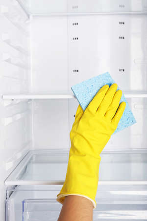Womans hand washing refrigerator with duster photo