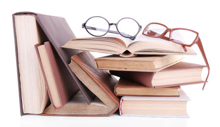 Books in a mess and pair of glasses isolated on white photo