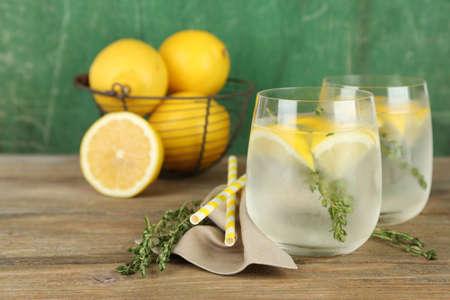 gaseosas: Bebida fría con sabor de limón y tomillo, sobre fondo de madera