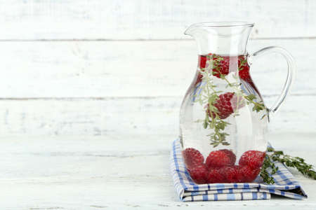 water thyme: Tasty cool beverage with raspberries and thyme, on light background