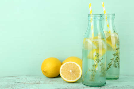 Tasty cool beverage with lemon and thyme, on wooden background Stock Photo