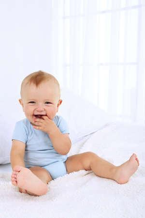 Mignon petit garçon sur le lit dans la chambre Banque d'images