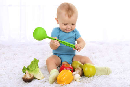 Cute baby boy with fruit and vegetables on carpet in room photo
