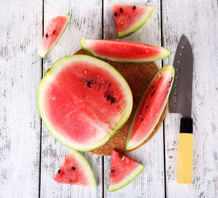 Watermelon and knife on cutting board on wooden background photo