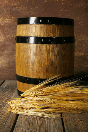 Barrel and ears on wooden table on wooden wall background photo