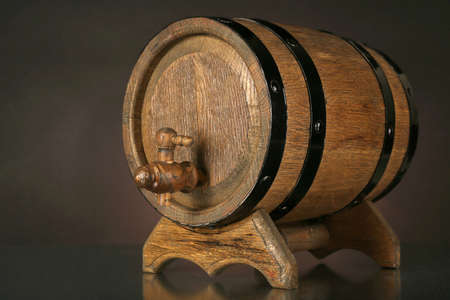Barrel on wooden table on dark background photo