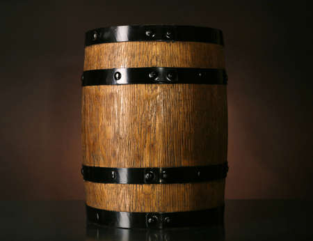 Barrel on wooden table on dark background photo