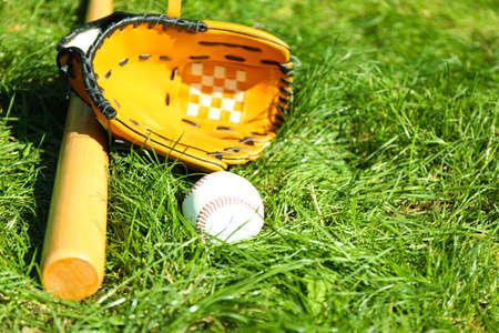 guante de beisbol: Bate de béisbol, pelota y guante en el fondo de la hierba verde