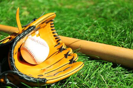 Baseball bat, ball and glove on green grass background photo