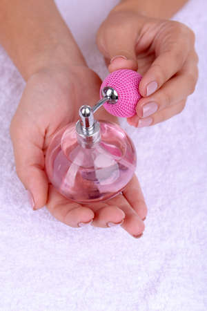 Woman hands holding perfume close up photo