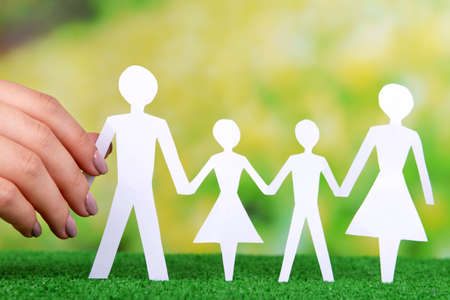 Woman hand holding paper family on grass on bright background photo