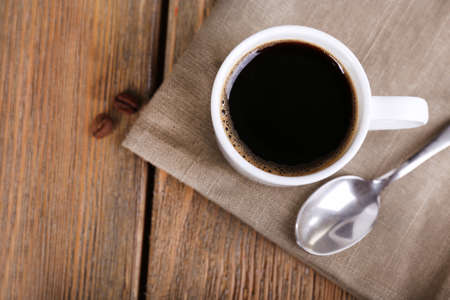 Cup of coffee and coffee beans on napkin on wooden background photo