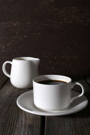 Cup of coffee and cream in milk jug on wooden table on dark background photo