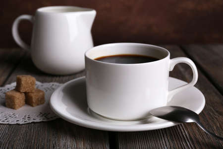 Cup of coffee with cream in milk jug and sugar cubes on wooden table on dark background photo