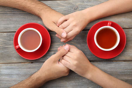 women holding cup: Loving couple with hot drinks on table