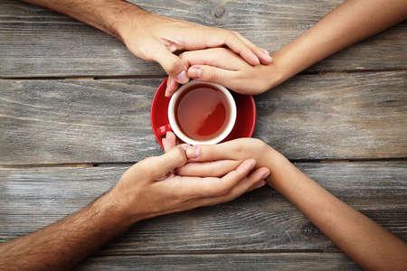 tasses de thé et se tenant la main à la table en bois