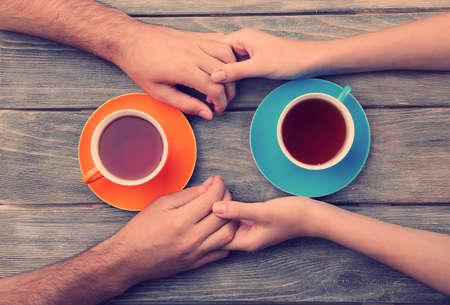 manos entrelazadas: Tazas de té y tomados de la mano en la mesa de madera Foto de archivo