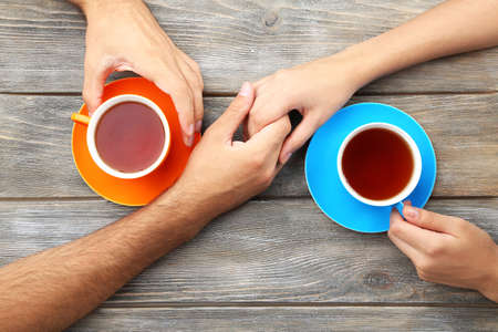 emotional love: Loving couple with hot drinks on table