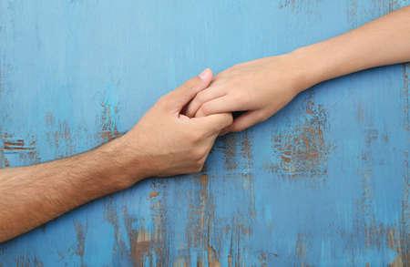 terra arrendada: Loving casal de mãos dadas close-up no fundo de madeira Imagens