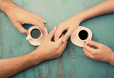 women coffee: Coffee cups and holding hands at the wooden table