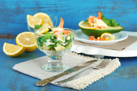 Tasty salads with shrimps and avocado in glass bowl and on plate, on wooden background photo