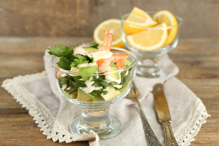 Tasty salad with shrimps and avocado, on wooden background photo