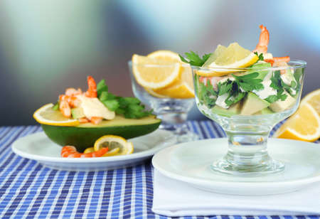 Tasty salads with shrimps and avocado in glass bowl and on plate, on table, on bright background photo