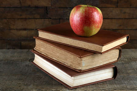 Apple with book on wooden background photo