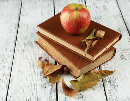 Apple with books and dry leaves on wooden background photo