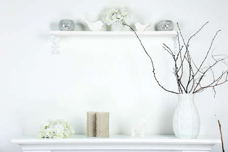 Different objects on white shelf in living room