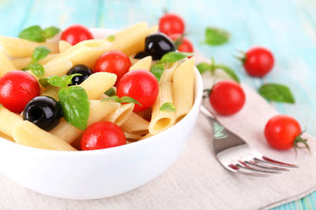 Pasta with tomatoes, olives and basil leaves in bowl on napkin on wooden background photo