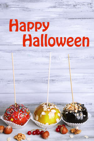 Sweet caramel apples on sticks with berries, on wooden table photo