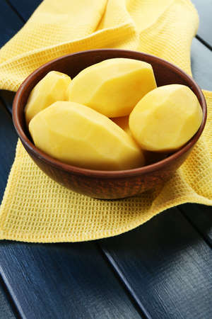Raw peeled potatoes in bowl  on color wooden background photo