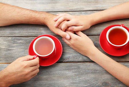holding arm: Loving couple with hot drinks on table