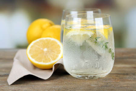 water thyme: Tasty cool beverage with lemon and thyme, on light background
