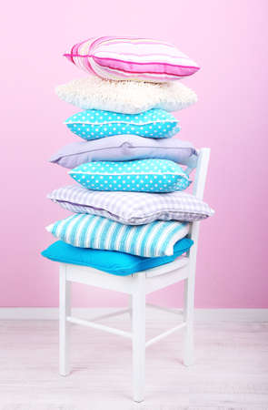 Bright pillows on chair in room on pink background photo