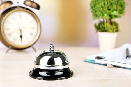 Reception bell on hotel reception desk, on bright background photo
