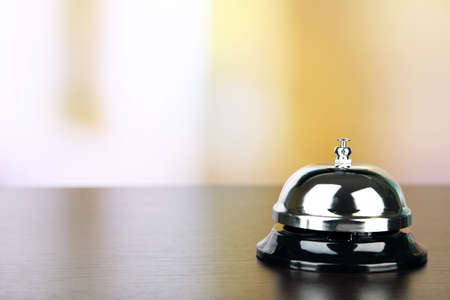 call bell: Reception bell on desk, on bright background Stock Photo