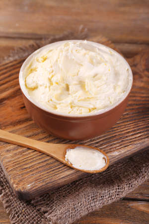 butterfat: Fresh homemade butter in bowl, on wooden background Stock Photo