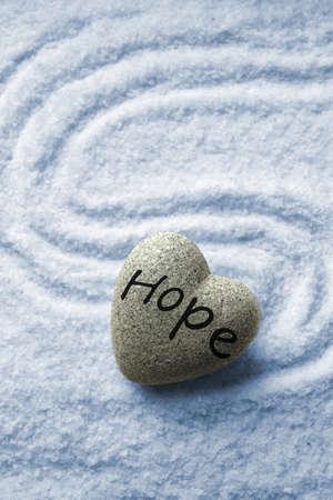Grey zen stone in shape of heart, on blue sand background photo