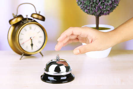 reception desk: Female hand ring bell on  hotel reception desk, on bright background Stock Photo