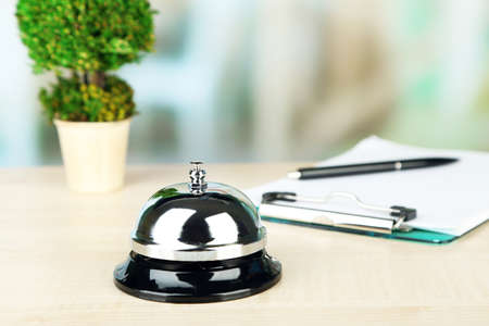 Reception bell on desk, on bright background photo